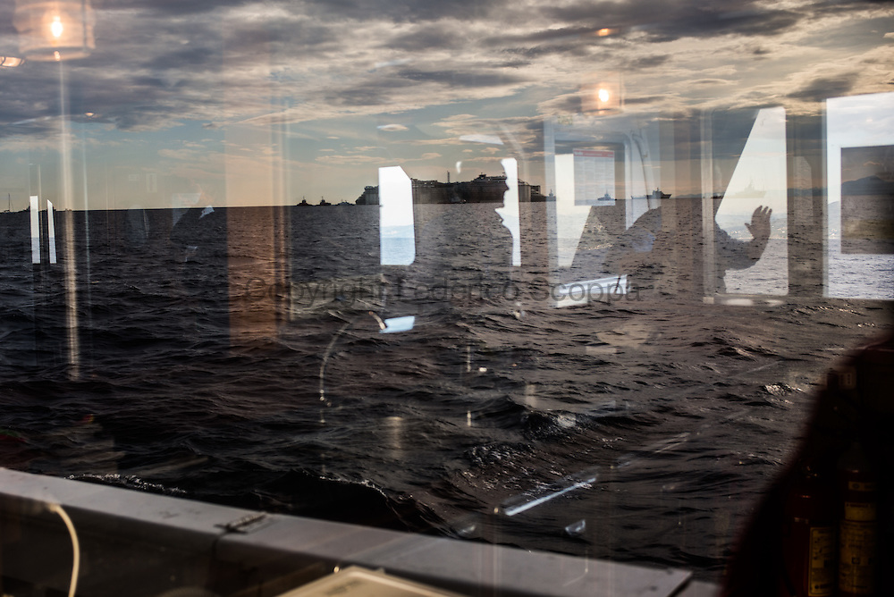 The Costa Concordia is seen on a reflection of a window