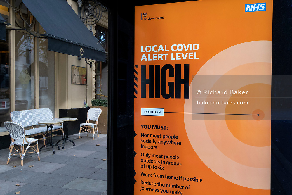 With empty tables outside an Aldwych bar, a government ad advises Londoners about the high alert level during the capital's Tier 2 restrictions, during the second wave of the Coronavirus pandemic, on 26th October 2020, in London, England.