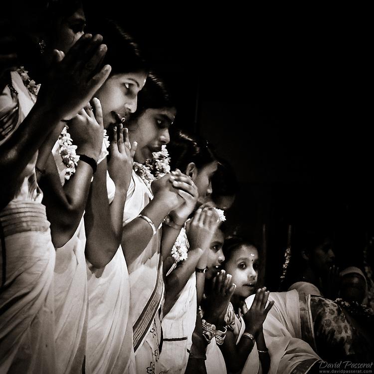 Teenage indian girls pray during holy celebration