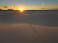Aerial view of a person standing alone in the middle of White Sands National Monument at sunset in Tularosa, USA.