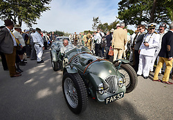 **CAPTION CORRECTION. Picture originally sent with wrong date. Picture was taken TODAY 11/09/2015** © licensed to London News Pictures. 11/09/2015<br /> Goodwood Revival Weekend, Goodwood, West Sussex. UK.<br /> The Goodwood Revival is the world's largest historic motor racing event. Competitors and enthusiasts dress in period fashions recreating the glorious days of the race circuit.<br /> Pictured. A classic MG enters the paddock before the next race.<br /> <br /> Photo credit : Ian Whittaker/LNP