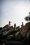 Three young women traveling in Southeast Asia, here atop a rocky outcrop at the beach on Mamutik Island in Kota Kinabalu, Sabah, Malaysia. (August 2019)