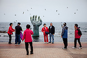 "People are photographing each other in front of the so called ""Hand of Harmony"" at Homigot beach close to Pohang at the South Korean East coast."