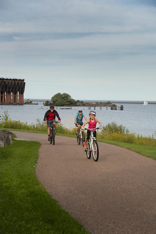 Family biking on the Iron Ore Heritage Trail along Lake Superior in Marquette, Michigan.