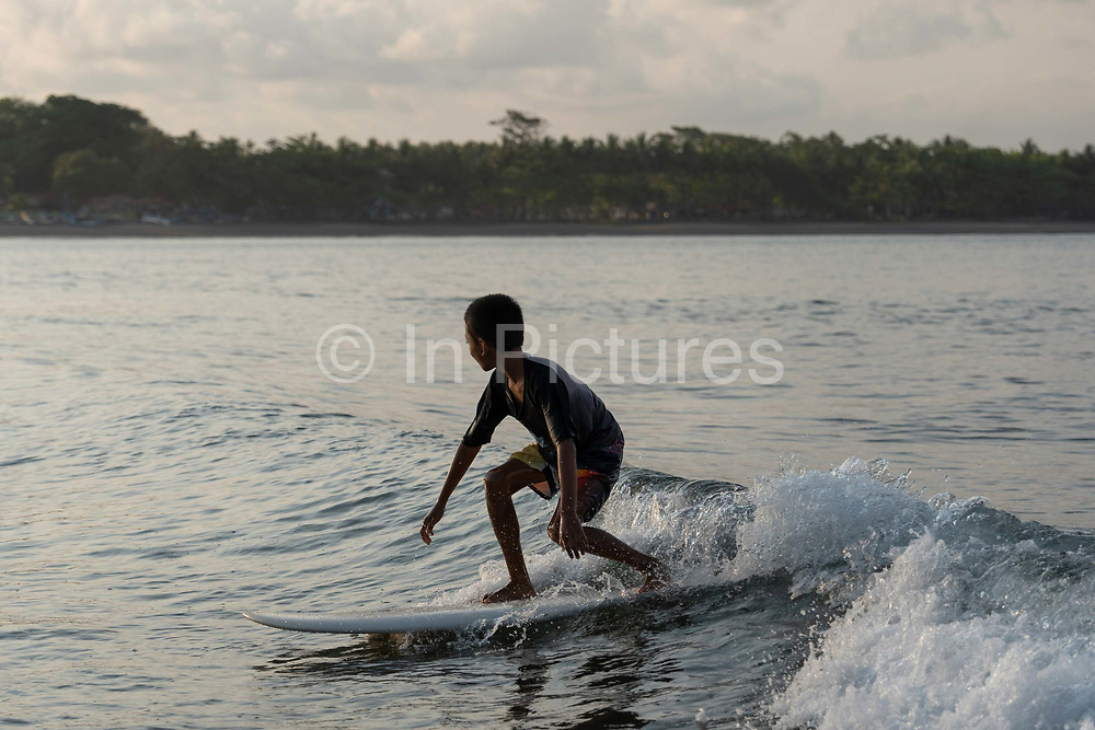 A young Indonesian boy surfing at Batu Karas beach on the 31st October 2019 in Java in Indonesia.