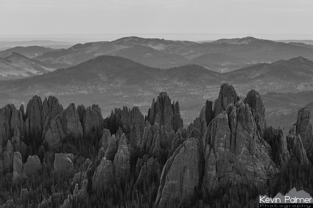 Sharp granite spires protrude out of the Black Hills as seen from the top of Harney Peak. The mountain was recently renamed to Black Elk Peak, and it is the highest in South Dakota. The jagged rock formations seen here are known as the Needles, and the Needles Highway winds around them with sharp switchbacks and narrow tunnels. This was the original location proposed for the Mount Rushmore carvings, but the sculptor rejected it because the granite was too soft. In the distance a forested hillside can be seen, scarred by the pine beetle infestation. In the last 20 years, 25% of the trees in the Black Hills have been killed by this destructive beetle.