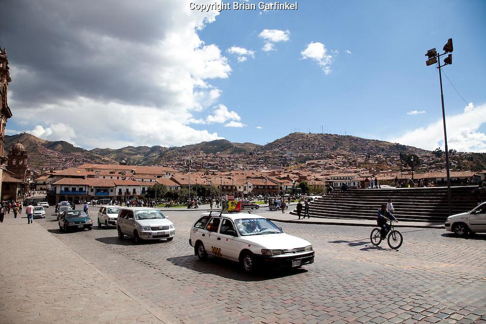 Cars drive through Plaze De Armas in Cusco Peru