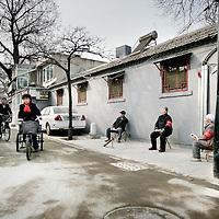 China,Beijing ,13 maart 2008..Chinese bewoners. wijkouderen, fietsers en werklieden in een gerenoveerde Huton (oud buurtje) in de oude stadswijk van Beijing..Dit is 1 van de weinig overgebleven Hutons van Beijing. De meeste oude wijkjes zijn met de grond gelijk gemaakt en hebben plaats gemaakt voor grote hogenieuwe kantoorgebouwen en flats..Met het vooruitzicht op de Olympische Spelen in augustus van dit jaar zijn enkele overgebleven Hutons gerenoveerd speciaal voor de toeristen.