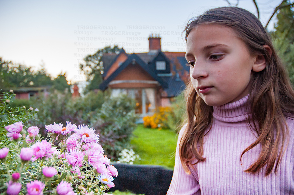 A young girl with long hair wearing a pink jumper in a country garden in England, UK