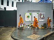 15 NOVEMBER 2015 - BANGKOK, THAILAND:  Buddhist monks walk past the gate of the French Embassy in Bangkok, Thailand. Security was heightened at the embassy after terrorists attacked civilian targets in Paris, France, on Nov. 13. The terrorists, affiliated with IS/ISIL killed more than 120 people. People left flowers at the gate to the embassy.         PHOTO BY JACK KURTZ