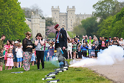Windsor, UK. 22nd April 2019. John Matthews, borough bombardier, supervises a child in firing a small cannon as part of a traditional 21-gun salute on the Long Walk in front of Windsor Castle for the Queen's 93rd birthday. The Queen's official birthday is celebrated on 11th June.