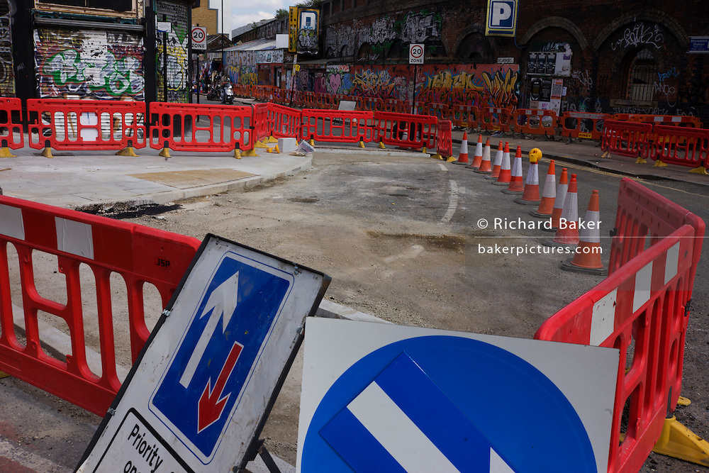 Roadworks signs and graffiti on a crossing in East London.