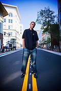 Hip Hop Producer 9th Wonder stands on a road that runs through his home town of Durham North Carolina.