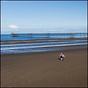 Couple walking on beach towards the pier