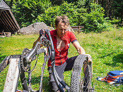 Mountain biker repairing bike in the forest, Baden-Wuerttemberg, Germany
