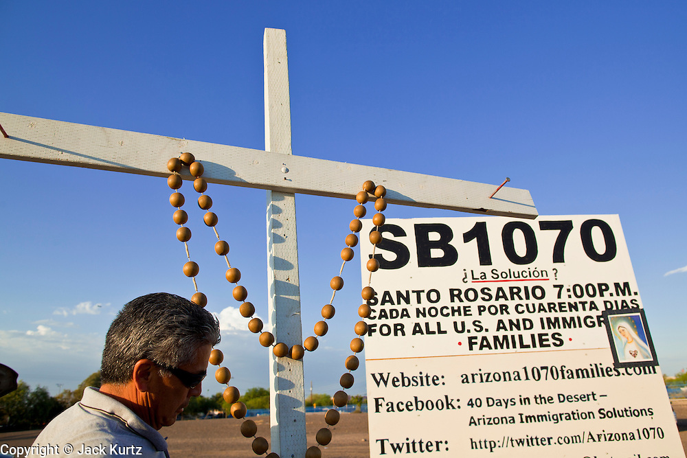 11 JULY 2010 - PHOENIX, AZ: A man walks by a cross during a rosary service against Arizona law SB 1070. About 40 people gather nightly at an intersection in an immigrants' neighborhood in Phoenix to pray the rosary in opposition to Arizona SB 1070, a law that requires local police to question the immigration status of people they have probably cause to believe might be in the US illegally. Probable cause can include a traffic stop like speeding or having a cracked windshield. The law is being challenged in federal courts by several parties, including the US Department of Justice, which claims the law is unconstitutional because only the federal government can enact and enforce immigration laws.      PHOTO BY JACK KURTZ