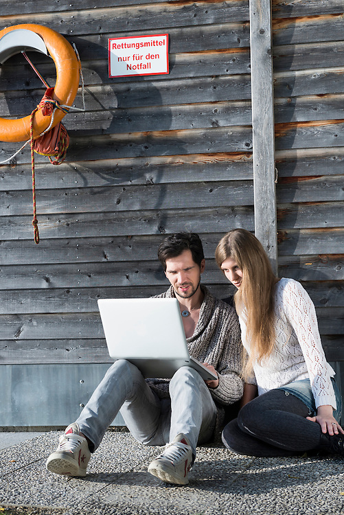 Young couple using laptop computer sitting outside