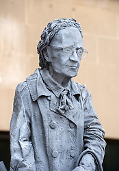 """© Licensed to London News Pictures. 24/04/2018. Bristol, UK. A statue of an elderly lady holding her handbag and a hammer has been put up on Victoria Street in Bristol city centre. The statue has """"OAP"""" with the """"A"""" as an anarchist symbol painted on the plinth, and has been chained to two bicycle stands outside the offices of Age UK. Staff working at Age UK Bristol found the 10-foot tall statue in front of their offices when they arrived at work on Monday, but know nothing about the statue. There have been unconfirmed reports the statue is a tribute to a lady by an anonymous artist, as the name """"Ruth"""" is written on the back of the plinth.  Photo credit: Simon Chapman/LNP"""