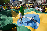 London, UK. Thursday 12th June 2014. Giant flag is held between the corwd. Brazilians gather for the Brazil Day celebrations in Trafalgar Sq. A gathering to celebrate the beginning of the Brazil 2014 FIFA World Cup. Revellers sing and dance and play football games and all in the yellow green and blue of the Brazilian flag.