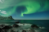 Northern lights fill sky over open sea and mountains, Flakstadøy, Lofoten Islands, Norway