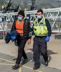 © Licensed to London News Pictures. 24/03/2021. Dover, UK. A man being escorted form a boat at Dover, Kent by a Border Force officer. Home Secretary Priti Patel has pledged an overhaul of asylum seeker rules, with refugees having their claim assessed based on how they arrive in the UK. Photo credit: Stuart Brock/LNP