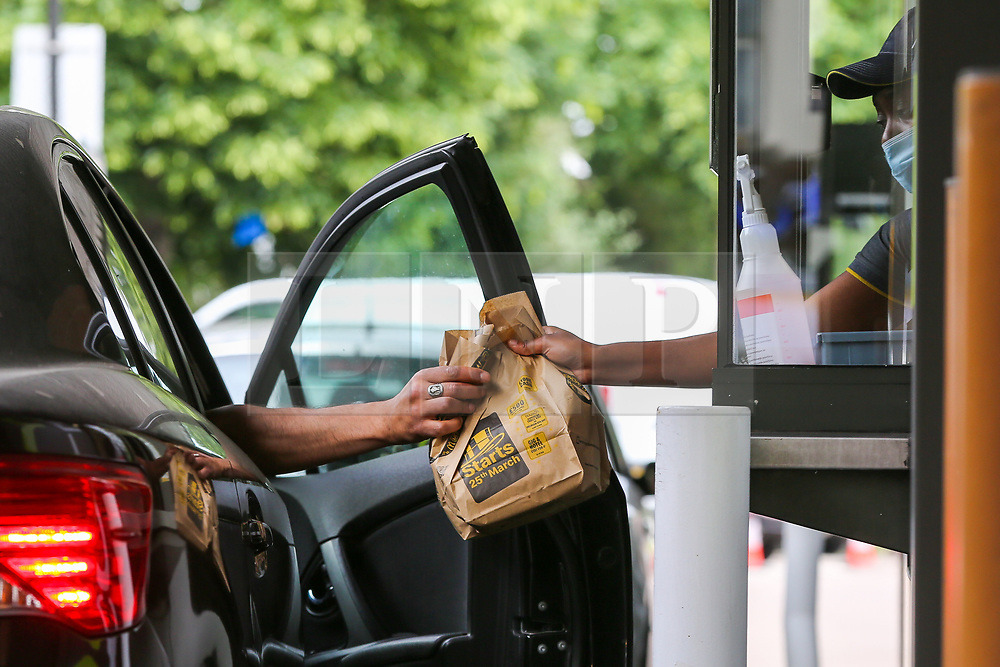 © Licensed to London News Pictures. 04/06/2020. London, UK. A staff member wearing face covering hands a meal bag to a customer at McDonald's Drive Thru in north London. McDonald's Drive Thru opens in Haringey after lockdown restrictions are relaxed.  <br /> <br /> ***Permission Granted***<br /> <br /> Photo credit: Dinendra Haria/LNP
