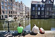 Nederland, Amsterdam, 7-5-2020  Twee schilders houden schaft, lunchpauze, en zitten op de kade van de oudezijds voorburgwal.Op de wallen is het sinds de coronacrisis erg stil en rustig. Omdat ze buiten werken en goed afstand kunnen houden zijn ze gewoon aan het werk .Foto: Flip Franssen
