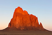 "Shiprock, a prominent peak located northwestern New Mexico, is turned golden at sunrise. The peak rises 1,583 ft (482 m) above the surrounding landscape and has a total elevation of 7,177 ft (2,188 m). The peak is located on Navajo tribal land and is sacred to them. The Navajo name for the peak is Tsé Bit'a'í, which means ""rock with wings."" Tribal legend says a great bird brought the Navajo people from the North to the present-day Four Corners area."