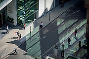 Looking down from an aerial view towards small business figures walking through green reflected light in the City of London, the capitals ancient financial district, on 13th May, in London, England.