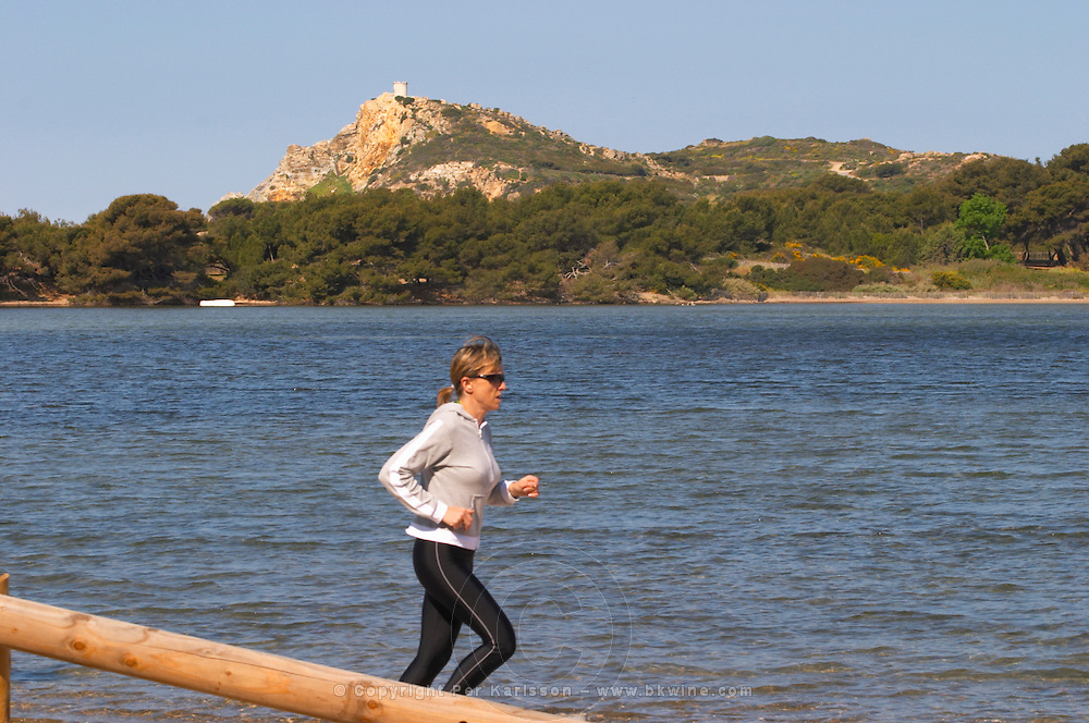 View from Sanary over the sea to the St Pierre des Embiez island, a woman in sun glasses and training clothes and large bosom jogging along the water Le Brusc Six Fours Var Cote d'Azur France