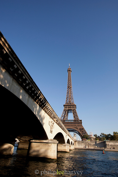 The iconic Eiffel Tower seen from over the banks of the River Seine at Pont d'Iena bridge in Paris, France