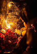 """15th January 2015, New Delhi, India. A woman lights an incense stick as part of her devotion as she asks for wishes to be granted by Djinns in the ruins of Feroz Shah Kotla in New Delhi, India on the 15th January 2015<br /> <br /> PHOTOGRAPH BY AND COPYRIGHT OF SIMON DE TREY-WHITE a photographer in delhi. + 91 98103 99809. Email:simon@simondetreywhite.com<br /> <br /> People have been coming to Firoz Shah Kotla to leave written notes and offerings for Djinns in the hopes of getting wishes granted since the late 1970's. Jinn, jann or djinn are supernatural creatures in Islamic mythology as well as pre-Islamic Arabian mythology. They are mentioned frequently in the Quran  and other Islamic texts and inhabit an unseen world called Djinnestan. In Islamic theology jinn are said to be creatures with free will, made from smokeless fire by Allah as humans were made of clay, among other things. According to the Quran, jinn have free will, and Iblīs abused this freedom in front of Allah by refusing to bow to Adam when Allah ordered angels and jinn to do so. For disobeying Allah, Iblīs was expelled from Paradise and called """"Shayṭān"""" (Satan).They are usually invisible to humans, but humans do appear clearly to jinn, as they can possess them. Like humans, jinn will also be judged on the Day of Judgment and will be sent to Paradise or Hell according to their deeds. Feroz Shah Tughlaq (r. 1351–88), the Sultan of Delhi, established the fortified city of Ferozabad in 1354, as the new capital of the Delhi Sultanate, and included in it the site of the present Feroz Shah Kotla. Kotla literally means fortress or citadel."""