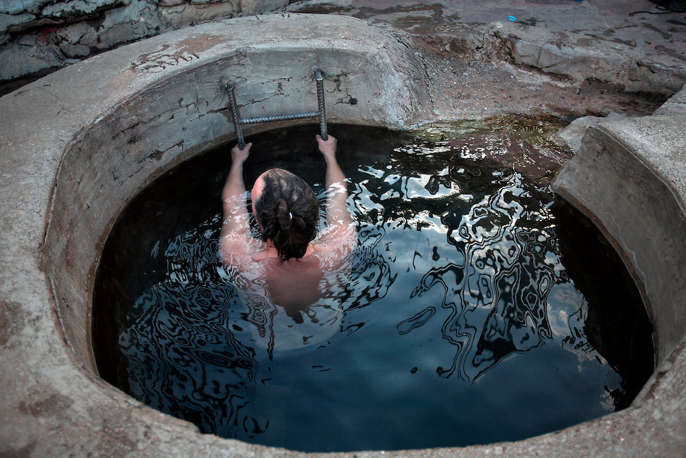 A man relaxes in natural hot-springs in Las Vegas, NM.
