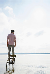 Young man standing chair lake alone thoughtful