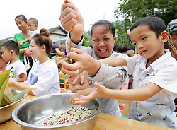 June 15, 2018 - Liping, Guizhou, China - Children learn to make Zongzi, a pyramid-shaped dumpling made of glutinous rice wrapped in bamboo or reed leaves, during an activity to celebrate upcoming Dragon Boat Festival at Ruizhi kindergarten. (Credit Image: © Yang Daifu/Xinhua via ZUMA Wire)
