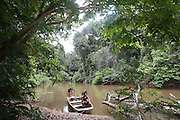 Surui indians with boat inside Surui territory, primary rainforest interior.<br /><br />An Amazonian tribal chief Almir Narayamogo, leader of 1350 Surui Indians in Rondônia, near Cacaol, Brazil, with a $100,000 bounty on his head, is fighting for the survival of his people and their forest, and using the world's modern hi-tech tools; computers, smartphones, Google Earth and digital forestry surveillance. So far their fight has been very effective, leading to a most promising and novel result. In 2013, Almir Narayamogo, led his people to be the first and unique indigenous tribe in the world to manage their own REDD+ carbon project and sell carbon credits to the industrial world. By marketing the CO2 capacity of 250 000 hectares of their virgin forest, the forty year old Surui, has ensured the preservation, as well as a future of his community. <br /><br />In 2009, the four clans and 25 Surui villages voted in favour of a total moratorium on logging and the carbon credits project. <br /><br />They still face deforestation problems, such as illegal logging, and gold mining which causes pollution of their river systems