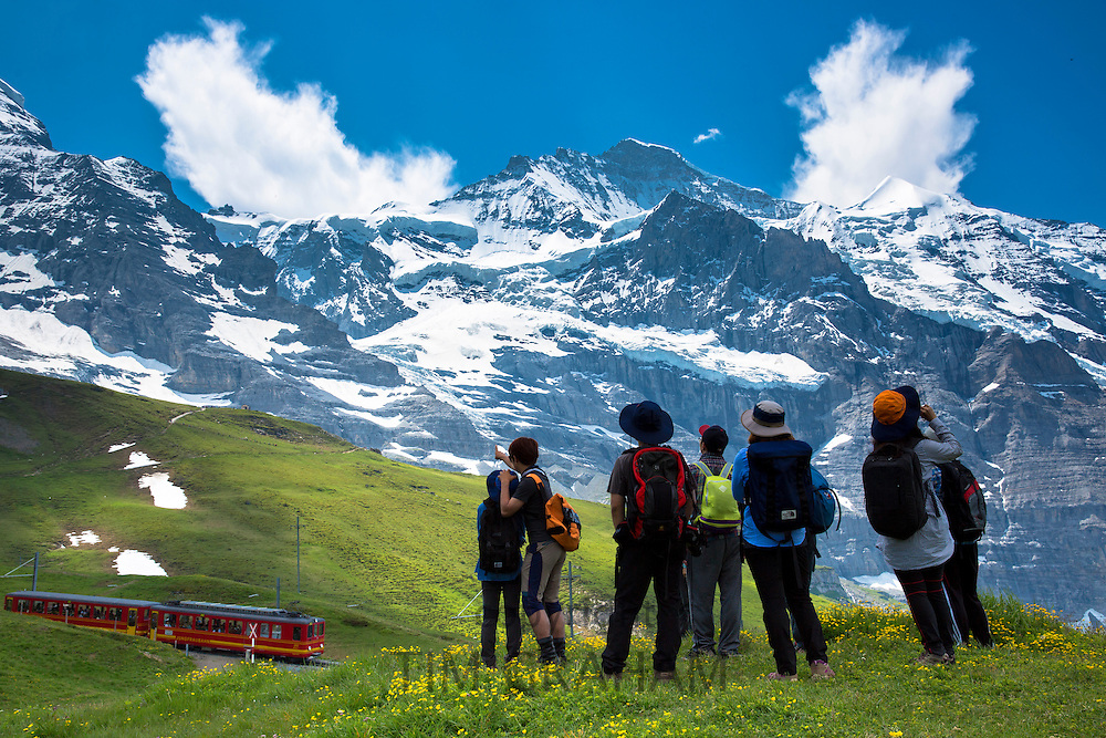 Japanese tourists viewing the Jungfrau mountain peak as avalanche rumbles in the Swiss Alps in Bernese Oberland, Switzerland