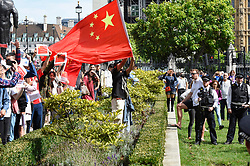 """© Licensed to London News Pictures. 17/08/2019. LONDON, UK.  Pro China demonstrators in Parliament Square take part in a counter protest against a solidarity rally for the people of Hong Kong.  Similar """"Global Solidarity with Hong Kong"""" rallies are taking place worldwide as protests in the former British colony enter their tenth week demanding democratic reforms and a halt to police brutality.  Photo credit: Stephen Chung/LNP"""
