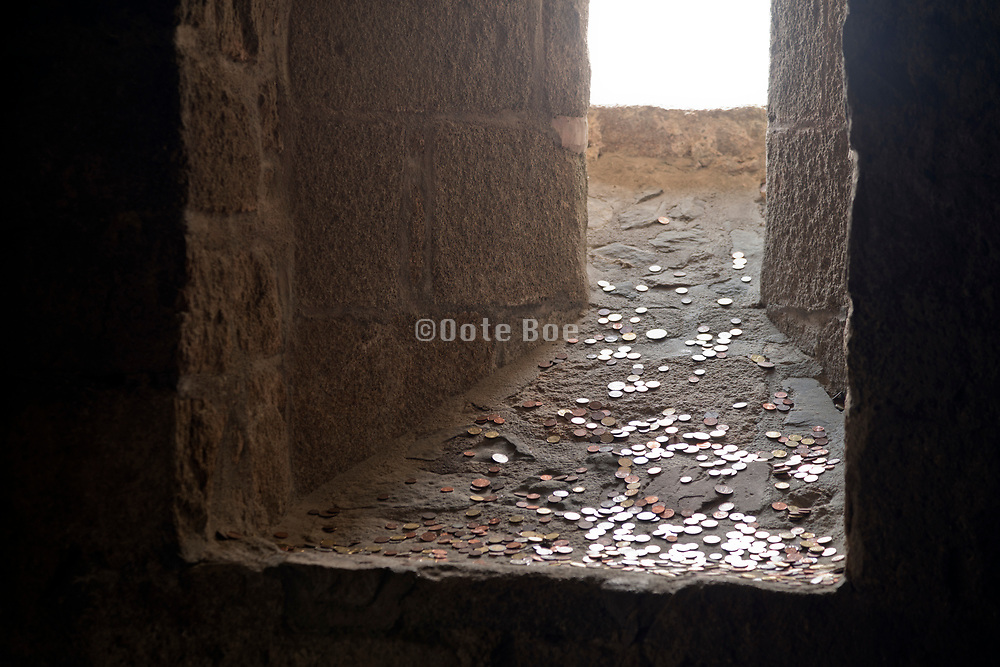 old castle window opening with good luck coins thrown on its ledge at Mont Saint Michel France
