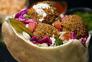 Falafel in pita bread with salad and Tahini sauce. Fried balls of patty made from spiced chickpeas. falafel is a popular form of fast food in the Middle East and is considered Israel's national food