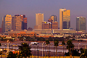 18 JANUARY 2011 - PHOENIX, AZ: Commercial airliners land at Phoenix Sky Harbor Airport, as the tall buildings east facing of downtown Phoenix reflect the sunrise over the city, Tuesday, Jan 18.  PHOTO BY JACK KURTZ