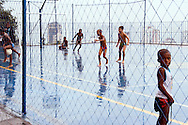 Kids playing football in the rain, at a youth centre in Cantagalo, Zone Sul, Rio de Janeiro, October 2006