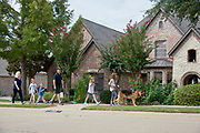 Paul and Brenda Chabot photographed with their four children as they walk their dog around their new neighborhood in McKinney, Texas on August 13, 2017. (Cooper Neill for The New York Times)