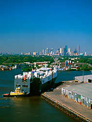 Aerial view of a shipping vessel in the Port of Houston with the Houston skyline in the background.
