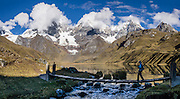Cordillera Huayhuash reflects in Carhuacocha lake (13,600 feet) at the outlet stream footbridge in the Andes Mountains, Peru, South America. Peaks from left to right are: Siula Grande, Yerupaja Grande (6635 m or 21,770 ft, highest point in the Amazon watershed), Yerupaja Chico, and Mount Jirishanca (Icy Beak of the Hummingbird). Day 3 of 9 days trekking around the Cordillera Huayhuash. This panorama was stitched from 2 overlapping photos.