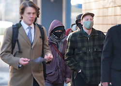 © Licensed to London News Pictures; 25/01/2021; Bristol, UK. Colston Four at court. MILO PONSFORD (right in baseball cap with green face mask) arrives at Bristol magistrates court. Defendants Rhian Graham, 29, Milo Ponsford, 25, Jake Skuse, 32, and Sage Willoughby, 21, are due before Bristol Magistrates' Court for their first hearing today. They have been charged with criminal damage in connection with damage to the statue of slave trader Edward Colston which was pulled down during a Black Lives Matter protest on June 7 2020 and then thrown into Bristol Harbour. Police launched an appeal to trace suspects after the event and ten people were located. Six people accepted a caution while four were referred to the CPS. The statue was later retrieved by Bristol City Council who say that the damage is costed at £3,750. Police have warned anyone planning to protest at the court hearing that they will be breaking the lockdown laws which prohibit public gatherings of more than two people to combat the Covid-19 coronavirus pandemic. Photo credit: Simon Chapman/LNP.