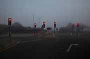 Thick fog at a junction with six traffic lights on red in London making a peaceful yet eerie landscape atmosphere as structures appear and disappear and infrastructure is releaved through a mist which lasted tthrough the entire day.