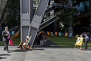 A lady holds a private conversation while seated in a deckchair on Leadenhall in the City of London, (aka The Square Mile) the capital's financial district, on 2nd September 2019, in London, England.