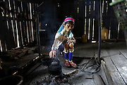 DEMOSO, April 11, 2016 (Xinhua) -- <br /> <br /> A Padaung woman with brass rings around her neck boils water at her home in Panpet village, Demoso township, Kayah state, Myanmar, April 11, 2016. The brass rings are first applied when the Padaung girls are about eight years old and as the girl grows older, longer coils are added up to 24 or 25 rings.<br /> ©Exclusivepix Media