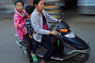Morning rush to school, mother and kids on the motorbike scooter, in the fishing harbour of Wai Luo Gang, Guangdong province, China